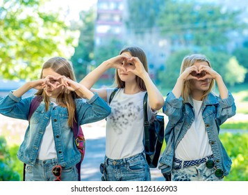Three girls schoolgirl. It's in nature. Gesture shows his heart with his hands. Dressed in jeans in clothes. The concept of love, best friends.