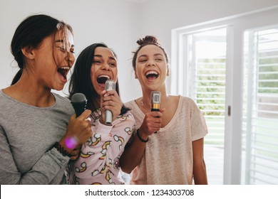 Three girls singing holding microphones standing in their room. Happy girls singing karaoke at a sleepover.