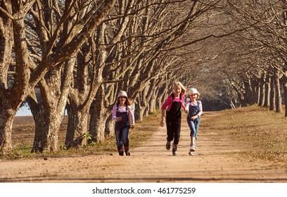 Three girls sisters kids running skipping down dirt road tree lined avenue