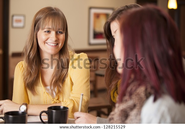 Three girls sit at a table with coffee and study.