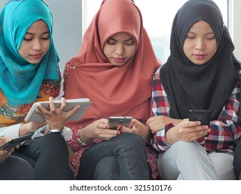 Three girls sitting together while playing their hand phones.