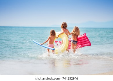 Three girls with swimming tools running to the sea