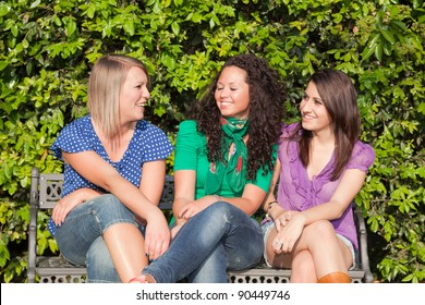 Three Girls Talking Seated on a Bench
