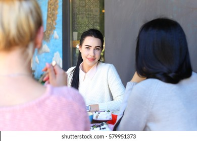 Three girls talking and sit in cafe. Attractive young adult girl with black hair smiling, tells story and something shows in phone to girlfriends background of wall in coffee shop. Girls with black