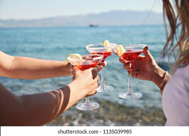 Three girls with their coctails at a beach party