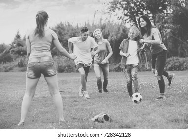 Three girls and two boys teenagers friends running with ball on meadow outdoors