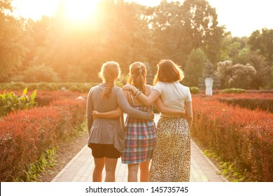 three girls walking in the sunset park