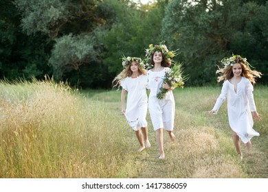 Three girls with wreaths of flowers in their hands. Midsummer. Earth Day.