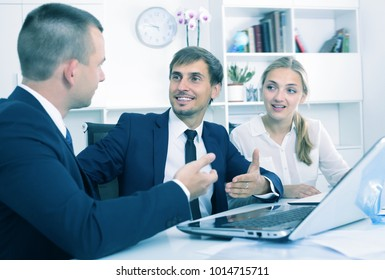 Three glad business male and female assistants in formalwear having a conversation in firm office