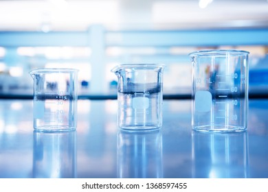 three glass beakers in chemical education science laboratory blue technology background
