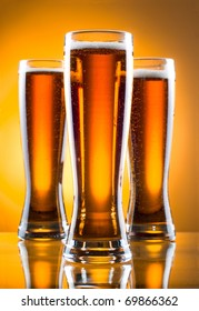 Three glass of beer over yellow background