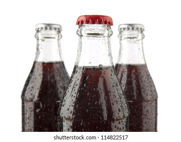 three glass bottles with cola on a white background , with no labels. Isolated on white background.