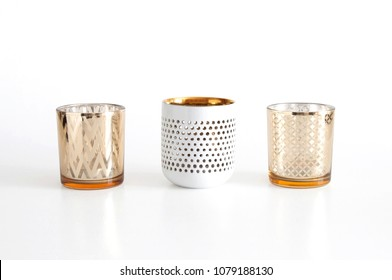 Three glass candle holders with candles, on white background. Clipping path