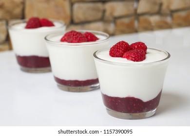 Three glass cups of fresh yogurt with fresh raspberries and raspberry jam