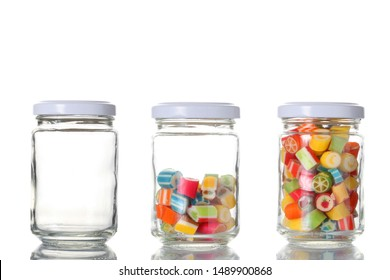 three glass jar, one empty, one half empty and one full of colored candies isolated on white background with clipping path and copy space for your text