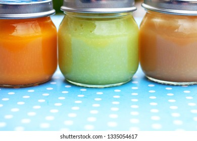 Three glass jars close up with baby puree for the first feeding up