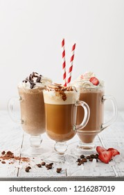 Three glass mugs with various coffee cocktails with cream and toppings on white background