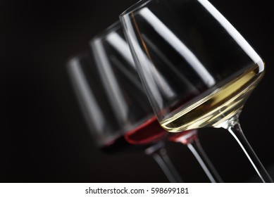 Three glass of red, rose and white wine over black background. Wine card menu design. Closeup of wineglasses with luxury wines for wine tasting.