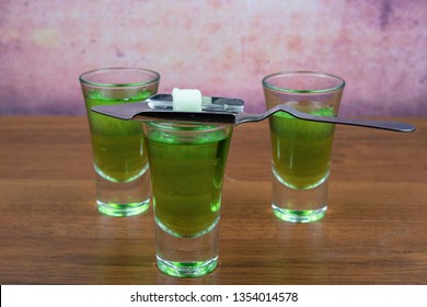 Three glasses with absinthe, a special spoon for absinthe and a piece of refined sugar
