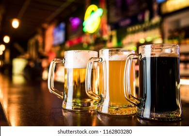 Three glasses of beer on a table in bar background