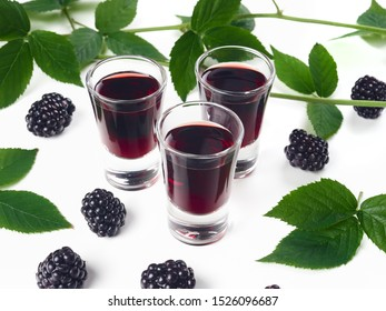 Three glasses of blackberry liqueur, also known as creme de mure, on white background, decorated with bramble sprigs and fresh blackberries