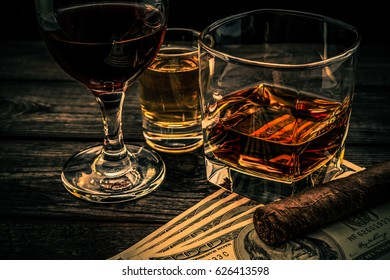 Three glasses with brandy, tequila and red wine with money and cuban cigar on an old wooden table. Angle view, focus on the cuban cigar, image vignetting and the orange-blue toning
