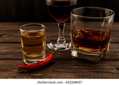 Three glasses with brandy, tequila and red wine with cayenne pepper on an old wooden table. Close up view