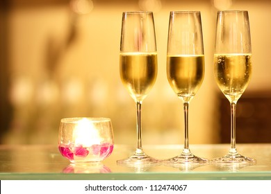 Three glasses of champagne with candle waiting to be served by guests in a restaurant