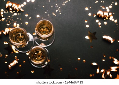 Three glasses of champagne with golden decoration. Top view, place for text. Festive concept.