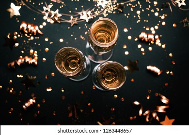 Three glasses of champagne on holiday black background with golden decoration. Top view. Festive concept.