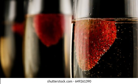 Three glasses with champagne with strawberries on a black background focus in the foreground
