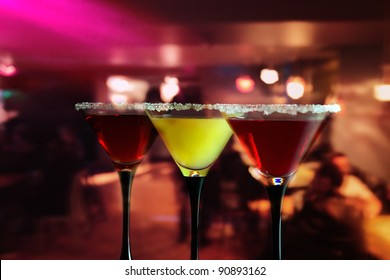 Three glasses with a cocktail in bar.