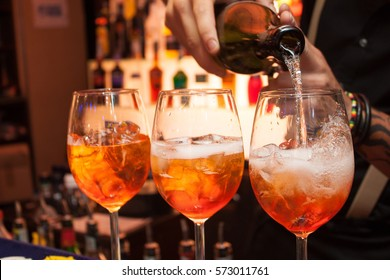three glasses of cocktails on the bar. bartender pours a glass of sparkling wine with Aperol.