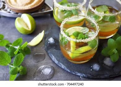 Three glasses of cold refreshing summer lemonade mojito on dark background