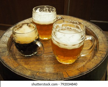 Three Glasses of Czech Beer Resting on a Wooden Barrel Table, Unfiltered Pilsner Style Lager, Two Half Litres of Light and One Small Glass of Dark, all Partly Drunk
