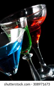 Three glasses of different alcoholic beverages on a black background close up