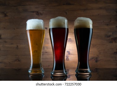Three glasses of different colored beer on wooden background