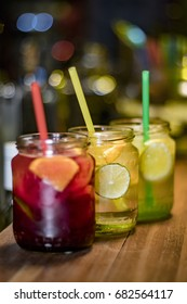 Three glasses of different flavored lemonades on the counter served in jars
