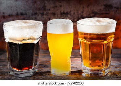 Three glasses with freshly poured light, unfiltered and dark beer on dark wooden desk. Food and beverages concept