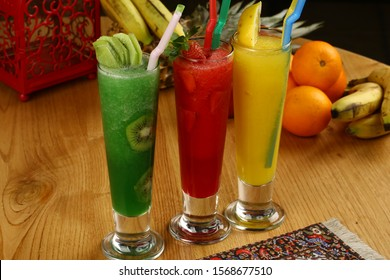 Three glasses of fruity juice with slices apple on wooden table. Strawbery juice, kiwi juice and lemonade with lime fruits