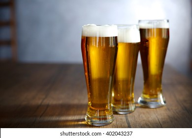 Three glasses of light beer on wooden table