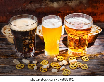 Three glasses with light, unfiltered and dark beer near plates with snacks, scattered small pretzels and pistachios on dark wooden desk. Food and beverages concept