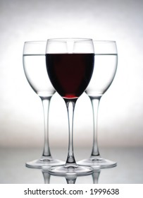 three glasses, one filled with wine and two others with water