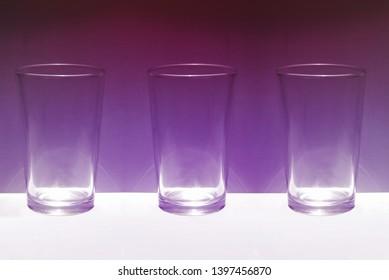 three glasses over purple background color
