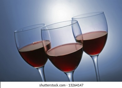 Three glasses with red wine on blue background