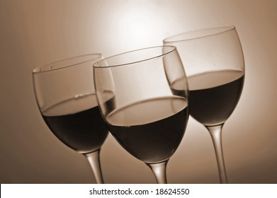 Three glasses with red wine on sepia background