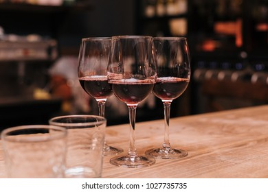 Three glasses of red wine stand on the bar
