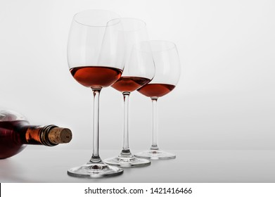 Three glasses of rose wine, a bottle and a cork in a white background in horizontal format