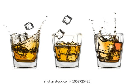 Three glasses of splashing whiskey with ice isolated on white