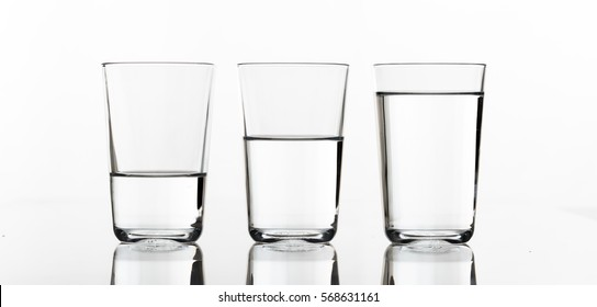 Three glasses of water, full, half, little,  isolated on white background, front view